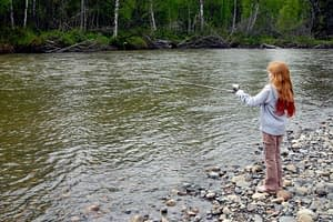 Girl_stands_on_shore_and_fishes_with_her_fishing_rod