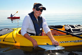 woman with fish in kayak